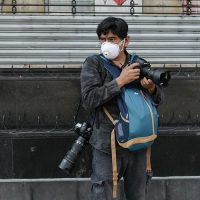 Mexican AFP photographer Alfredo Estrella wears a face mask as he works during the pandemic of the novel coronavirus COVID-19, in Mexico City, on April 8, 2020. (Photo by PEDRO PARDO / AFP)